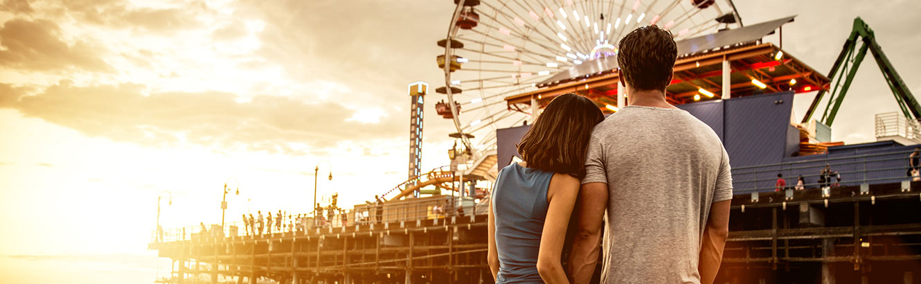 Couple from behind looking at pier and carnival rides.